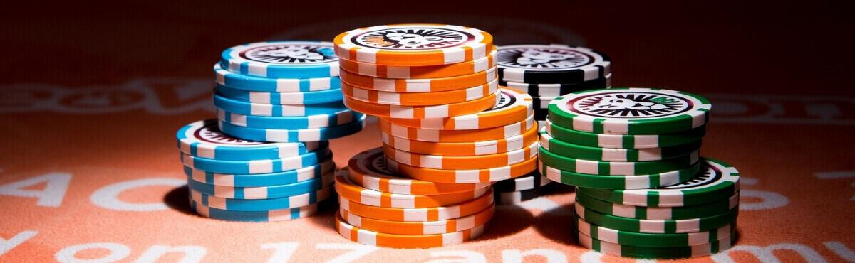 Roulette chips på et orange spil bord.